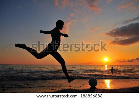 Two Guys playing at the ball on the coast of the sea in sunset