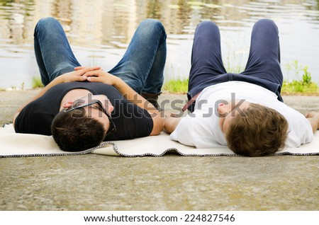 Two guys relaxing together lying in their jeans on a blanket alongside a river or lake - stock photo