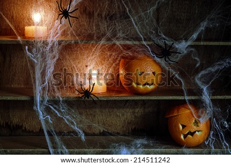 Two Halloween Jack o Lanterns Carved from Oranges and Spiderwebs with Spiders and Lit Candles on Shelves - stock photo