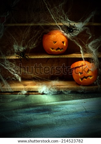 Two Halloween Jack o Lanterns Carved from Oranges and Spiderwebs with Spiders on Shelves Blurred in Background with Foreground Space - stock photo