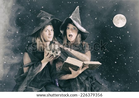 two halloween witches saying a magic formula to poison an apple - stock photo