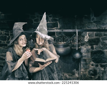 two halloween witches whispering a magic formula to poison an apple - stock photo