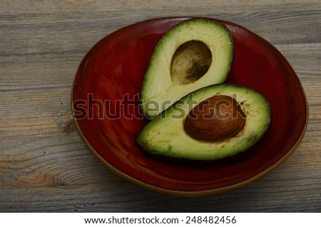 two halves of fresh avocado on red ceramic bowl - stock photo