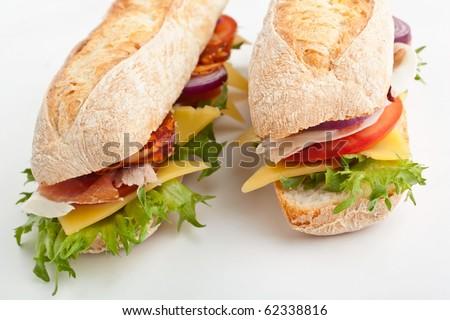 two halves of long white wheat baguette sandwich - stock photo