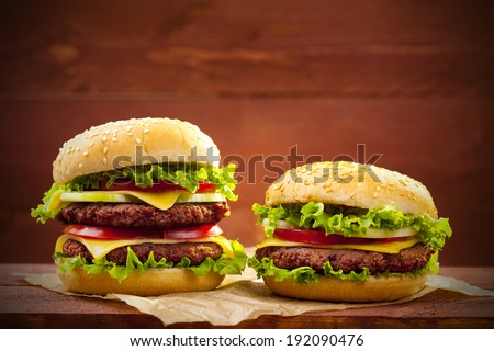 Two hamburgers on wood board