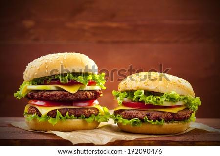 Two hamburgers on wood board - stock photo