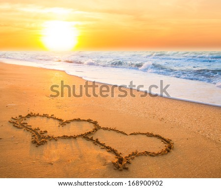 two hand drawn hearts on beach sand over sunset - stock photo