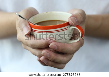 two hand hold warm a cup of coffee with foam over wooden table,  orange white ceramic coffee cup in winter