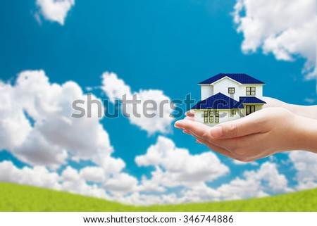 Two Hand holding house model on beautiful sky background - stock photo