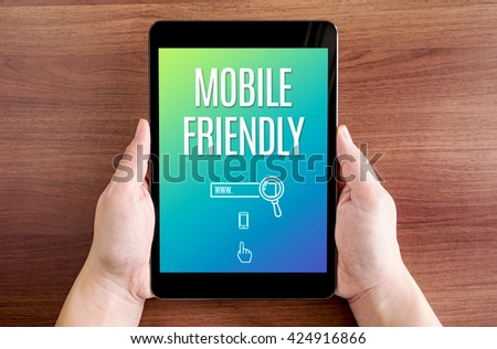 Two hand holding tablet with mobile friendly and icon on screen at dark brown table top,Digital business concept - stock photo