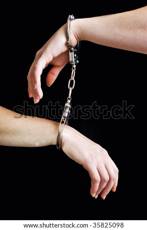Two hand shackled with handcuffs - stock photo