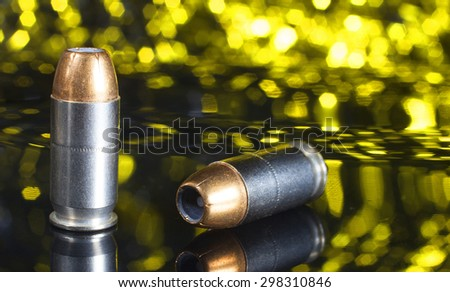 Two handgun cartridges with hollow point bullets and a yellow background - stock photo