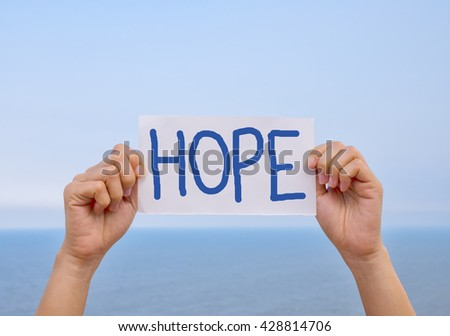 "Two handles paper wrote , "" hope "" held up . Background bright sky and sea ."