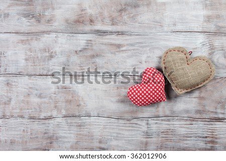 Two handmade Valentines Day hearts on wooden background - stock photo