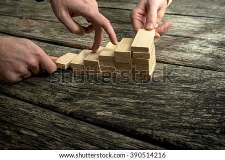 Two hands assembling a staircase of wooden pegs for the third one to walk its fingers upwards in a teamwork and support concept. - stock photo