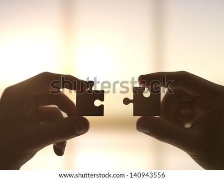 two hands collect puzzle, closeup - stock photo