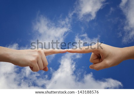Two hands connected with fingers. Cloudy sky in background. - stock photo