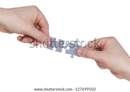 Two hands connecting puzzle pieces. Isolated on white background - stock photo