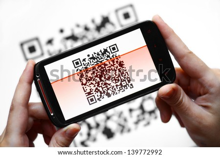 Two hands holding a mobile phone scanning a QR code - stock photo
