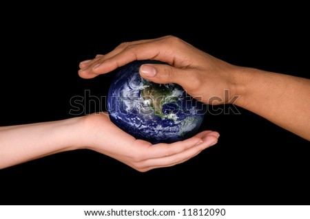 two hands holding a planet earth on black - stock photo