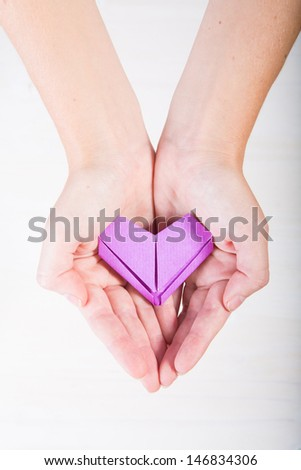 Two hands holding a purple origami heart - stock photo