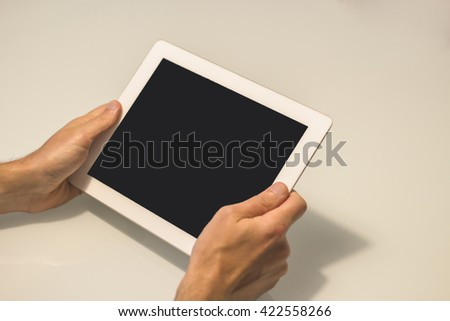 Two hands holding a tablet in a horizontal position. The device has a black screen and the background is white.