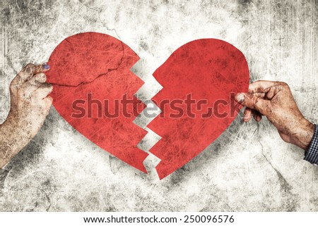 Two hands holding broken heart against grey background