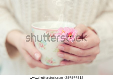 Two hands holding chamomile spring tea in a cup