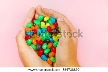 Two Hands holding many brightly coloured candy beans on a pale pink background - stock photo