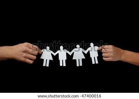 Two hands holding paper people - stock photo