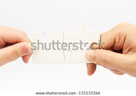Two hands holding puzzle pieces and connecting them - stock photo