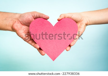 Two hands holding red paper love heart shape on blue background. Love concept. - stock photo