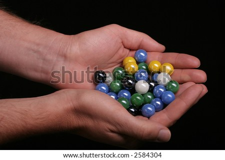 Two hands holding some colourfull marbles against a black background - stock photo