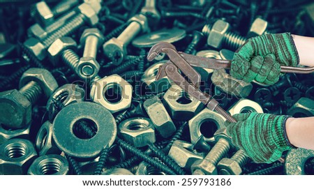 two hands holding the adjust spanner on used nut and bolts for equipment industrial background - stock photo