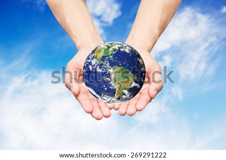 Two hands holding the earth on blue sky backgrounds.Elements of this image furnished by NAS