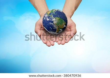 Two hands holding the earth on blurred map over beautiful blue sky backgrounds.safe healing planet:world earth day 22 April concept:love and protection global:Elements of this image furnished by NASA. - stock photo