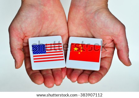Two hands holds the national flags of the United States of America (L) and of the Republic People of China (R) beside each other on a white background. Foreign relationship policy concept - stock photo