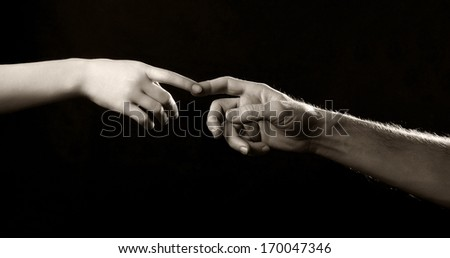 two hands, male and female, touch each other on a black background
