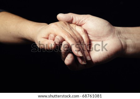 Two hands of senior people holding each other on a black background - stock photo