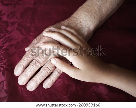 Two hands. Old and young. Child's hand on arm of an mature woman - stock photo