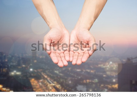 Two hands open palm gesture on blurred night city background - stock photo
