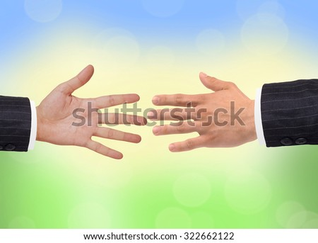 Two hands over bright nature background - stock photo