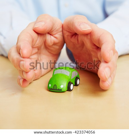 Two hands overing safety for a small green car