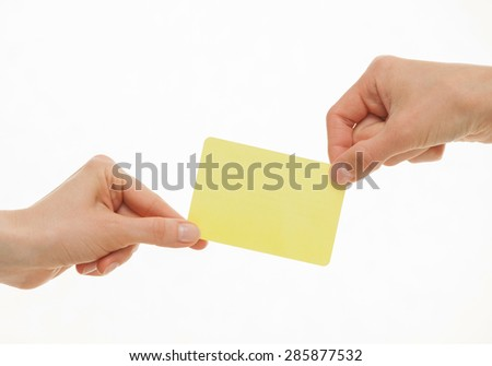 Two hands pull in different directions an yellow visiting card, white background