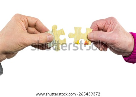 Two hands uniting fitting puzzle pieces. A male and a female hand both join with a piece of a puzzle as symbol or concept of solving a problem. Helping with a solution. Isolated on white background - stock photo