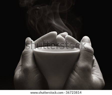 Two hands with an hot cup of coffee black and white - stock photo