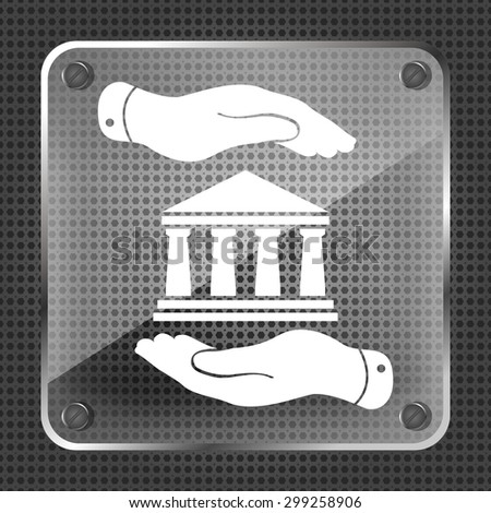 two hands with badge with bank icon on a metallic background - stock photo