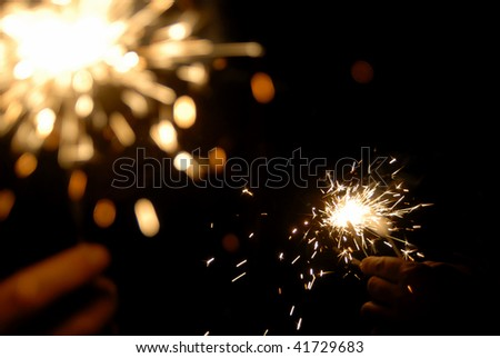two hands with bright new year sparklers in the dark - stock photo