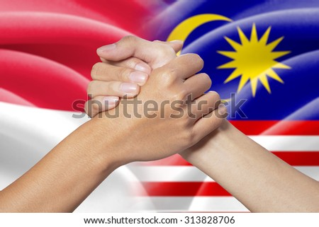 Two hands with partnership poses in front of the indonesian and malaysian flags - stock photo