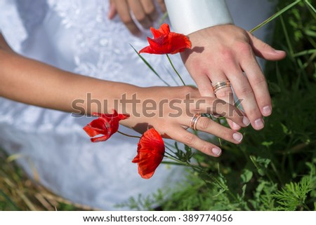 Two hands with wedding rings and poppies